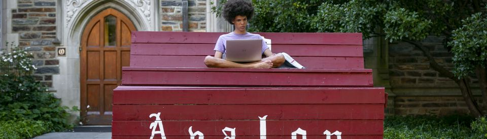Student with Laptop on bench in Duke Qaud